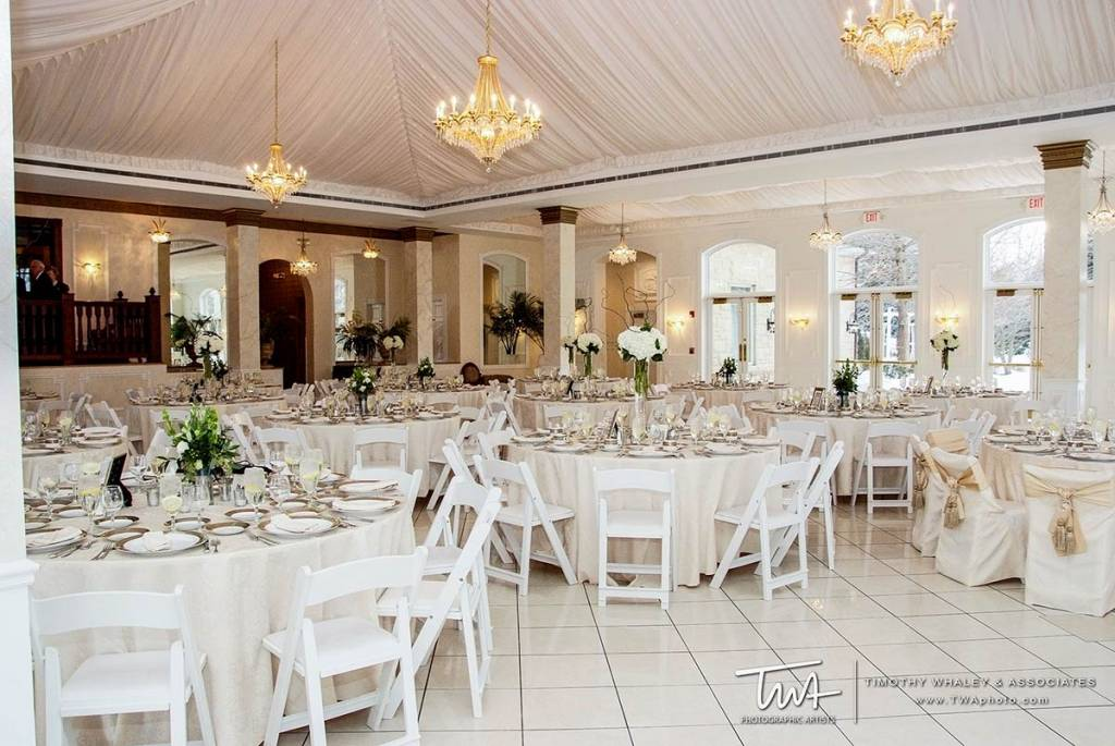 private ballroom filled with decorated tables for wedding
