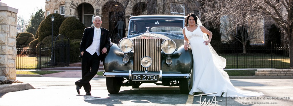 couple standing by a vintage car in front of castle banquet hall